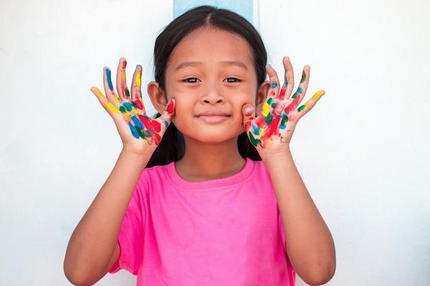 Niña linda con las manos pintadas coloridas en fondo de la pared