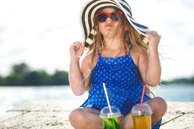 Niña linda en el mar. chica del sombrero en verano. adorable niño en la costa.