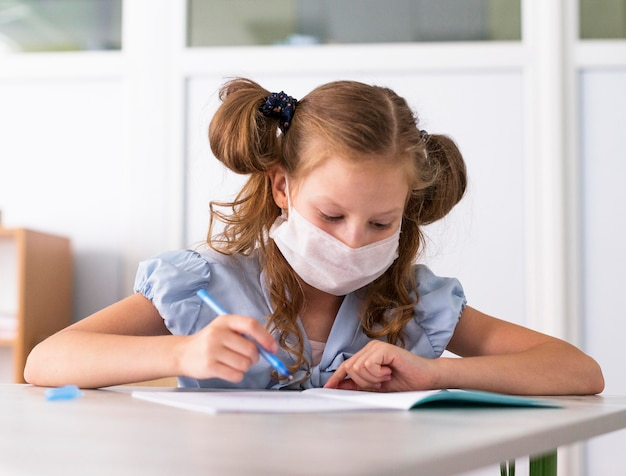 Niña linda con una máscara médica mientras escribe