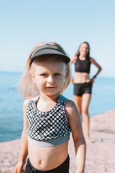 Niña linda mirando a la cámara sobre fondo de forma mamá en la playa