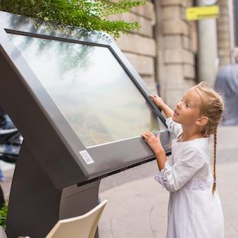 Niña linda mirando el mapa de milán