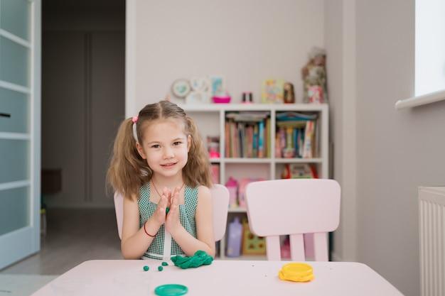 Niña linda moldes de plastilina en la mesa