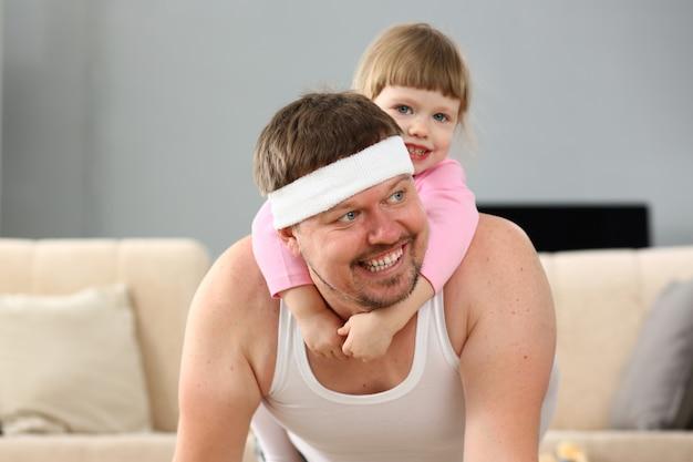 Niña linda montando a su padre en casa jugando