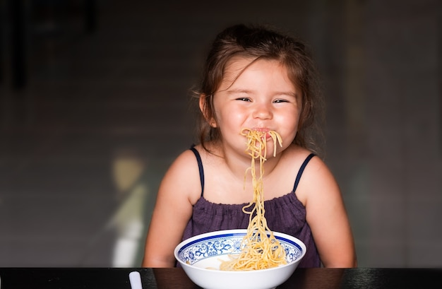 Niña linda niño comiendo espaguetis y sonriendo