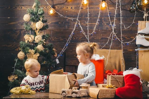 La niña linda del niño está decorando el árbol de navidad en el interior. niños de navidad. retrato de niño feliz mirando bola de juguete decorativa por árbol de navidad
