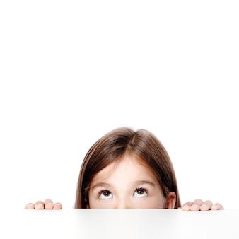 Niña linda del niño mirando hacia arriba sobre el escritorio en la escuela.