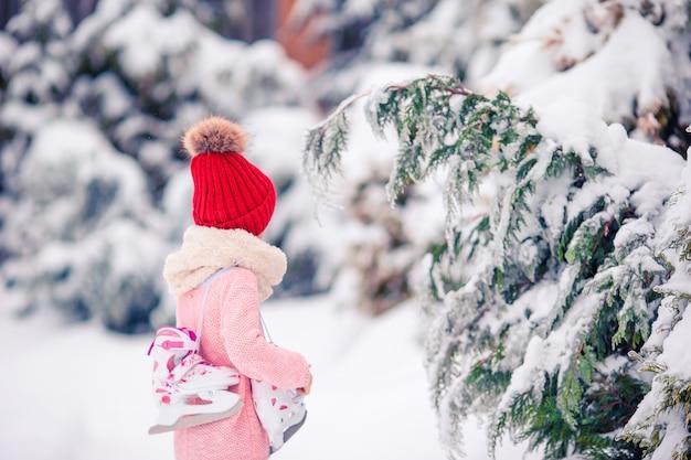 La niña linda del niño va a patinar al aire libre.