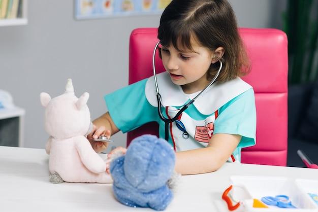 La niña linda del niño usa la ropa médica que juega el juego como médico veterinario que sostiene el estetoscopio que escucha el juguete enfermo