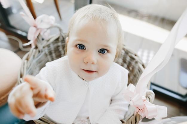 Niña linda con ojos azules se sienta en una canasta