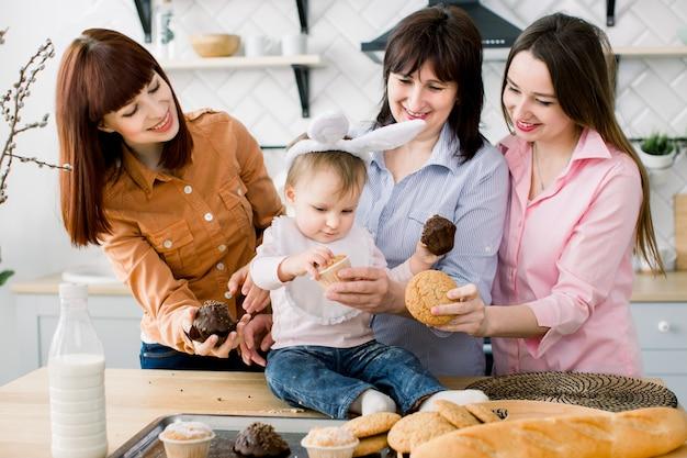 Niña linda con orejas de conejo en la cabeza y su hermosa mamá, tía y abuela están comiendo pastelitos que sostienen en sus manos. vacaciones de pascua o dia de las madres