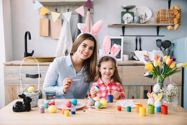 Niña linda en orejas de conejo pintando huevos para pascua con madre