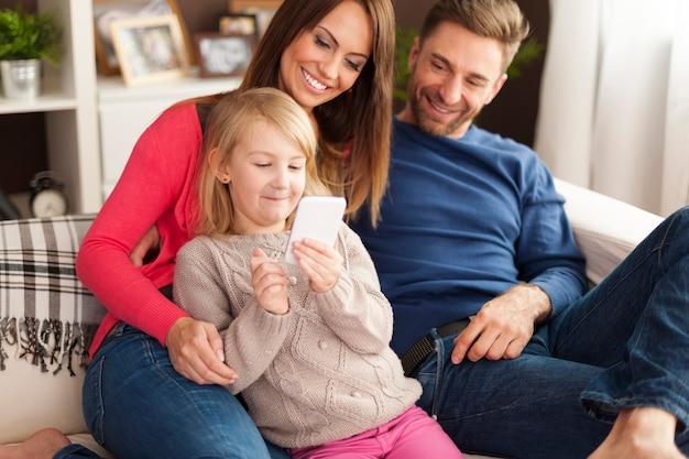 Niña linda con padres jugando por teléfono móvil en casa