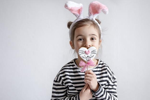 Niña linda con pan de jengibre de pascua en un palo y orejas de conejo decorativas en la cabeza.