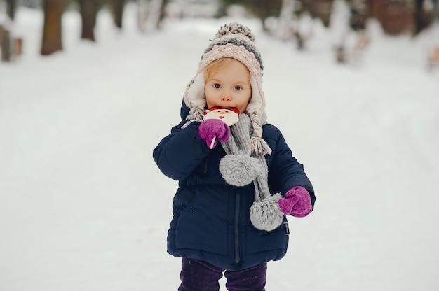 Niña linda en el parque de invierno