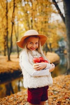 Niña linda en un parque de otoño