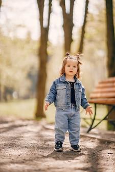 Niña linda en un parque de primavera