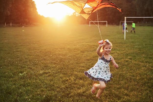 Niña linda con el pelo largo con cometa en el campo en un día soleado de verano
