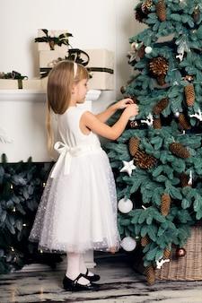 Niña linda con el pelo largo que adorna el árbol de navidad.
