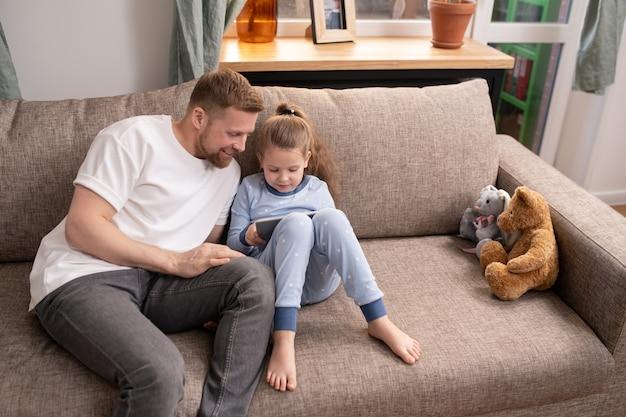 Niña linda en pijama azul y su padre feliz en ropa casual sentado en el sofá y viendo películas en línea en el panel táctil en casa