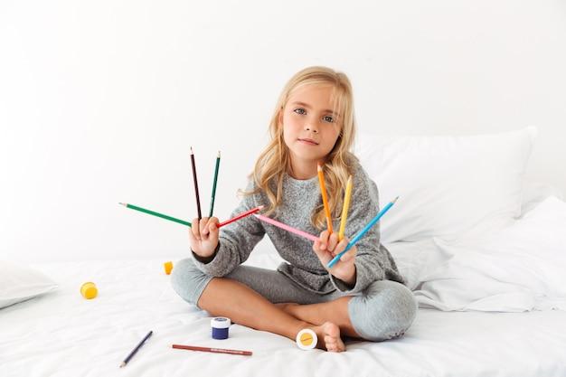 Niña linda en pijama gris mostrando sus lápices de colores en el dormitorio