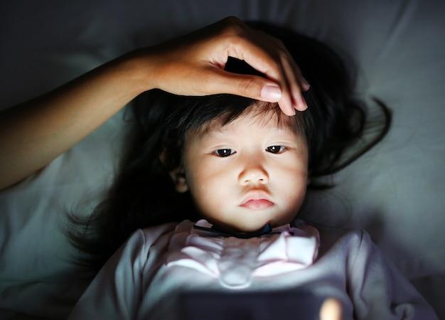 Niña linda en pijama jugando smartphone acostado en una cama con la mano de la madre acariciar una cabeza