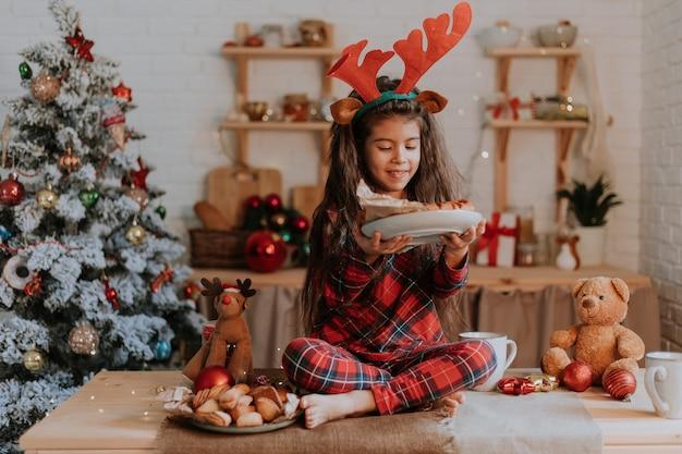 Niña linda en pijama rojo a cuadros con cuernos de ciervo en la cabeza está comiendo un pastel de navidad