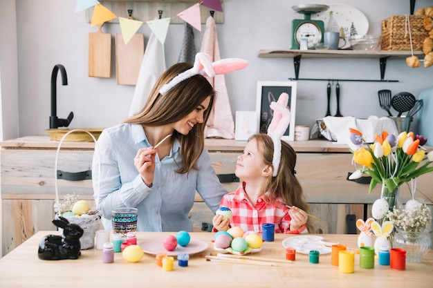 Niña linda pintando huevos para pascua con madre