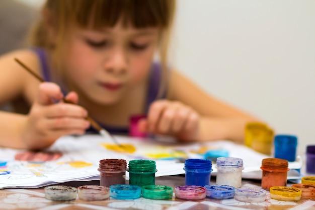 Niña linda pintando con pincel y pinturas de colores