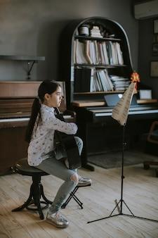 Niña linda practicando con una guitarra acústica en casa