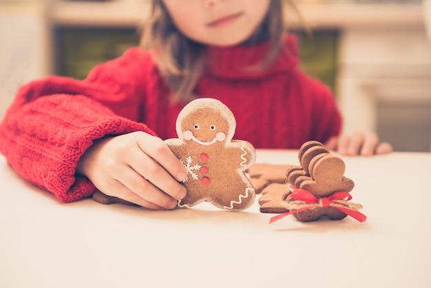 Niña linda prepara a hombres de pan de jengibre para las vacaciones de navidad