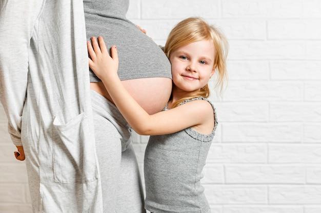 Niña linda que abraza el vientre embarazado de la madre