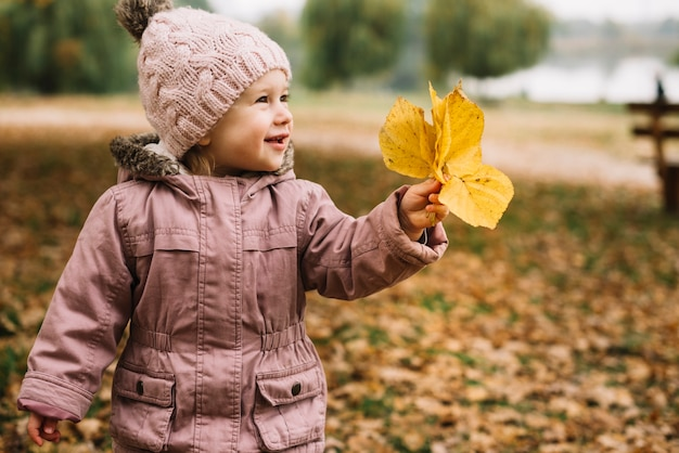 La niña linda que ase hojas amarillas en parque del otoño