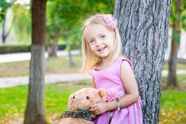 Niña linda que coloca el árbol cercano con su oso de peluche