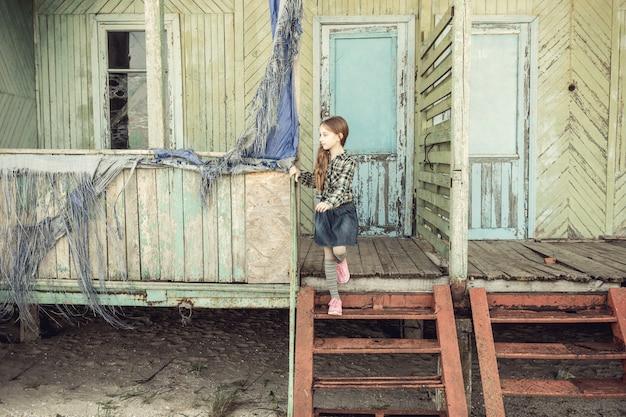 Niña linda que se coloca en las escaleras de la casa de madera abandonada