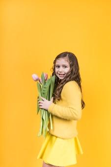 Niña linda que se coloca con los tulipanes rosados