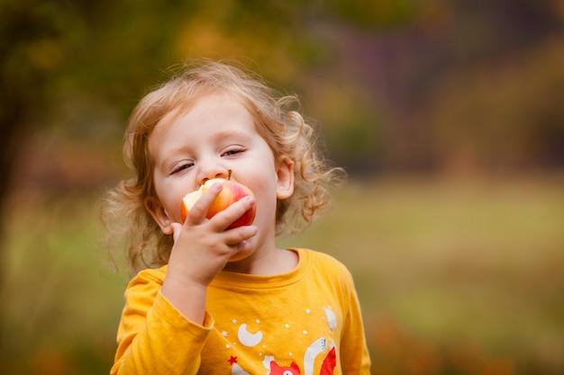 Niña linda que come la manzana red delicious
