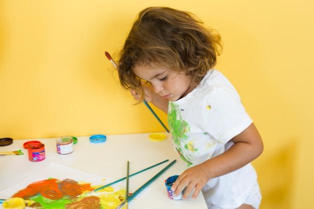Niña linda que dibuja con pinturas de colores