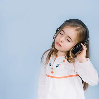 Niña linda que disfruta de la música en el auricular contra fondo azul