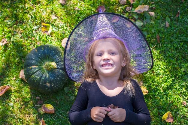 Niña linda que se divierte en halloween en traje de bruja