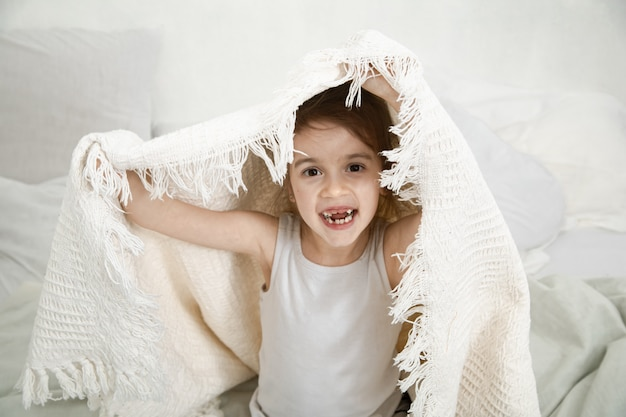 Niña linda que juega en cama con una manta.