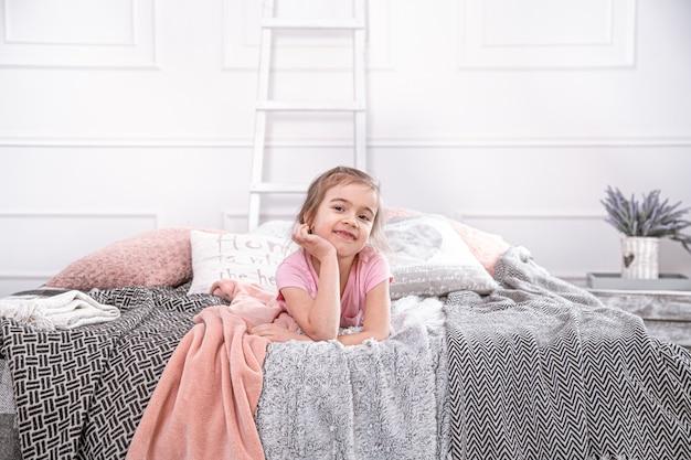 Niña linda que juega en la cama. mira pensativamente y descansa.