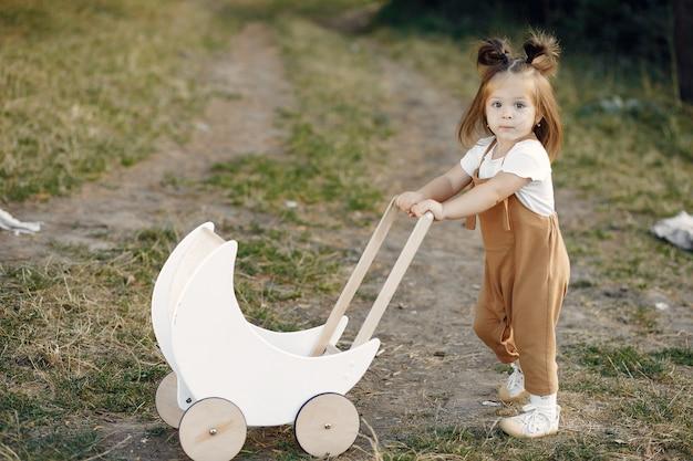 Niña linda que juega en un parque con el carro blanco