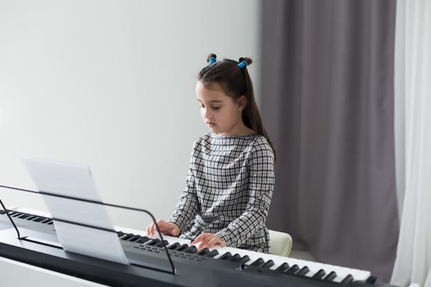 Niña linda que juega en el piano, sintetizador. formación. educación. colegio. entrenamiento estético. aula de primaria.