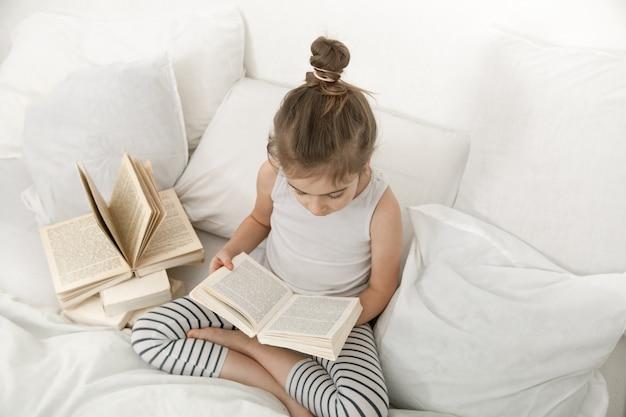 Niña linda que lee un libro en la cama en el dormitorio.