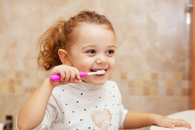 Niña linda que limpia el diente con el cepillo.