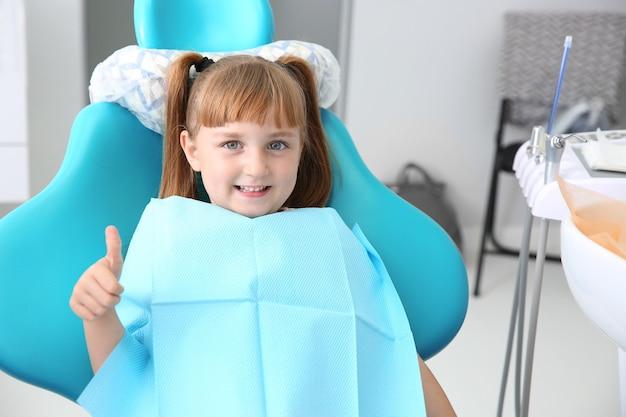 Niña linda que muestra el gesto del pulgar hacia arriba en el consultorio del dentista