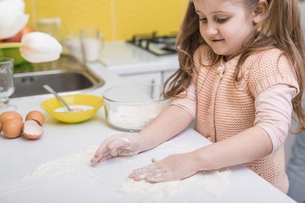 Niña linda que pone la harina en la mesa