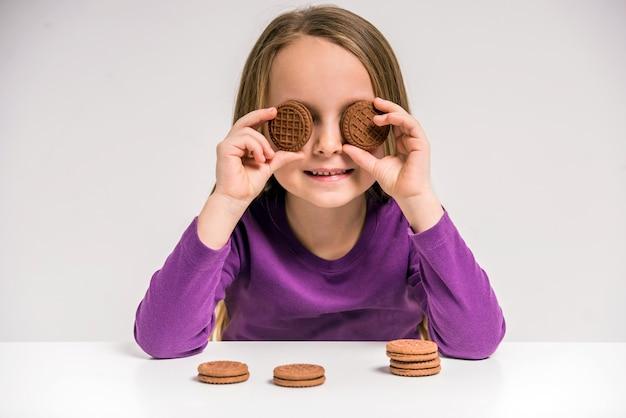 Niña linda que sostiene la galleta en la tabla.