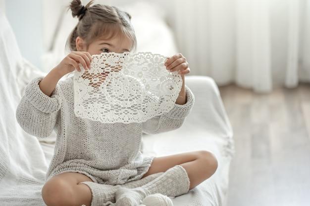 Niña linda que sostiene una servilleta calada hecha a mano en sus manos.
