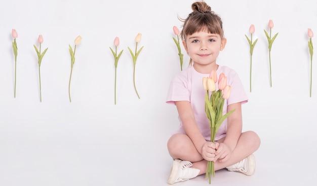 Niña linda que sostiene tulipanes